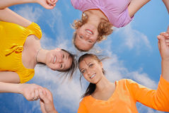 Friends. Three happy teenage girlfriends holding hands over blue sky background Stock Photo