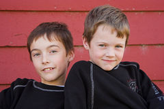 Friends. Two boys and red barn background Royalty Free Stock Photos