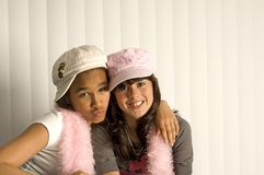Friends. Two teen girls hugging like friends with hats Stock Photo