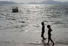 Friends. Two girls are strolling along Golden Zone beach in Acapulco, Mexico stock image