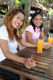 Friends. Two pretty Asian friends having a drink at a cafe Royalty Free Stock Images