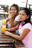 Friends. Two pretty Asian friends having a drink at a cafe Stock Images
