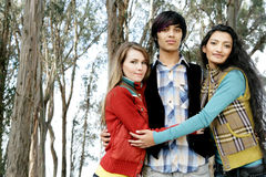Friends. Two young women and a young man standing in the woods Stock Photography