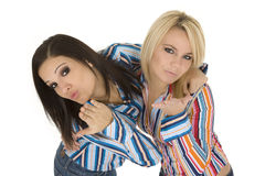 Friends. Female Caucasian friends acting silly blowing kisses on white background Royalty Free Stock Image