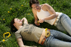 Friends. Two girls enjoying their freetime laying in the grass Royalty Free Stock Photo