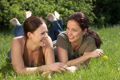 Friends. Two girls laying in the grass smiling Royalty Free Stock Images