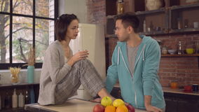 Friends in apartment talks in kitchen. Young woman holding glass with water sitting on the table talking with boyfriend. Happy family enjoy conversation in the stock footage