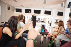 Friends Applauding For Woman in Bowling Club Stock Photography