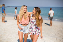 Friends with arm around walking on shore at beach. Happy female friends with arm around walking on shore at beach stock photography