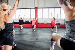 Friends With Arms Raised Exercising In Gym Stock Photography