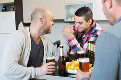 Friends armwrestling at the table Royalty Free Stock Photography