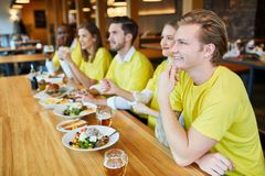 Friends as fans look a team`s game. Friends as fans in jerseys look a team game in the restaurant royalty free stock image