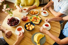 Free Friends At Round Table With Tea And Snacks Royalty Free Stock Image - 153840576