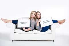 Friends with attitude. Two caucasian friends sitting with their bare feet over a big white couch sticking their tongues out in attitude wearing matching gray stock images