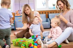 Friends with babies toddlers playing on the floor in sitting room. Female friends with kids toddlers playing on the floor in sitting room royalty free stock image