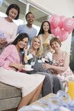 Friends At Baby Shower. Group of diverse friends with pregnant women at a baby shower stock photo