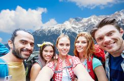 Friends with backpack taking selfie over mountains Stock Photo