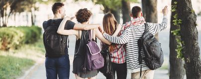 Friends with backpacks hugging walking in the city. Friendship, togetherness, traveling, vacation, holidays, sightseeing, city tour, student exchange program Stock Photography