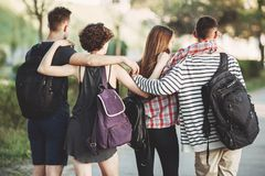 Friends with backpacks hugging walking in the city. People travel, vacation, holidays, friendship, city tour. Friends travelers with backpacks hugging and Royalty Free Stock Photography