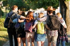 Friends with backpacks hugging walking in the city royalty free stock photography