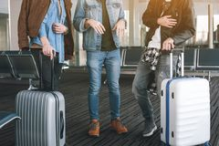 Friends with baggages situating in airport. Close up male legs standing near luggages in hall. Journey concept Stock Photos