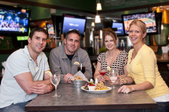 Friends in the bar. Group of friends having fun in a trendy bar stock image