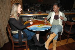 Friends at the Bar. Two beautiful friends sitting in a table in a restaurant having a fun chat and drinking martinis Royalty Free Stock Photo