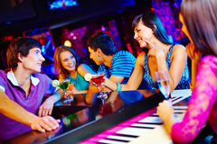 Friends at bar counter. Young people drinking and talking at nightclub stock photo