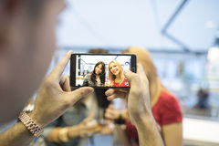 Friends in bar taking photos with smartphones Royalty Free Stock Image