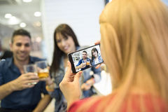 Friends in bar taking photos with smartphones Stock Images