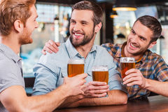 Friends in bar. Three happy young men in casual wear talking and drinking beer while sitting at the bar counter together Royalty Free Stock Photo