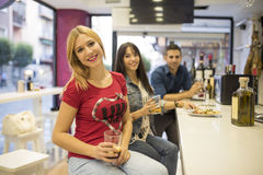 Friends in bar, three young people drinking Royalty Free Stock Photos