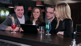 Friends at the bar. Two couple of young people looking at a tablet computer stock video footage