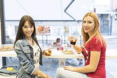 Friends in bar, two girls drinking in restaurant Royalty Free Stock Image