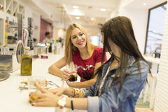 Friends in bar, two girls drinking in restaurant Stock Image