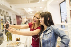 Friends in bar, two girls drinking in restaurant Stock Photos
