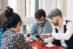 Friends in a bar using mobiles. Group of young friends using cellphones while having a coffee in a cafe bar royalty free stock image