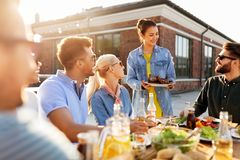 Friends at barbecue party on rooftop in summer royalty free stock images
