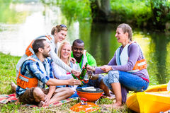 Friends barbecue after sports in forest drinking beer Royalty Free Stock Photography