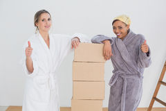 Friends in bathrobes with boxes gesturing thumbs up in new house Royalty Free Stock Image