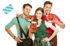 Friends in Bavaria with beer. Smiling friends in Bavaria with beer and pretzel holding bavarian flag Royalty Free Stock Photos