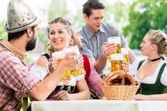 Friends in Bavarian beer garden drinking in summer Stock Photo