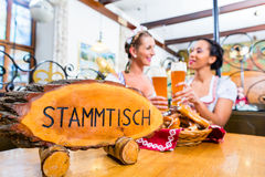 Friends in Bavarian inn toasting with beer glasses. Sitting at the Stammtisch royalty free stock images