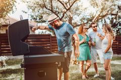 Friends at bbq party enjoying drinks and having a good time while cooking royalty free stock photos