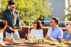Friends at bbq party on rooftop in summer royalty free stock images