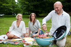 Friends with BBQ picnic in Park Stock Images