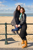 Friends on the beach. Two friends posing at the beach on a beautiful autumn afternoon royalty free stock images