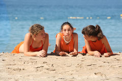 Friends on the beach. Three girls in orange clothes on the beach Stock Photography