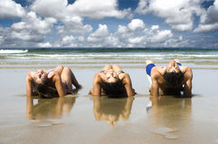 Friends on the beach. Three best friends seated on the sand having fun on the beach Stock Photos