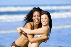 Friends at the beach. Two happy diverse friends playing at the beach Stock Photos